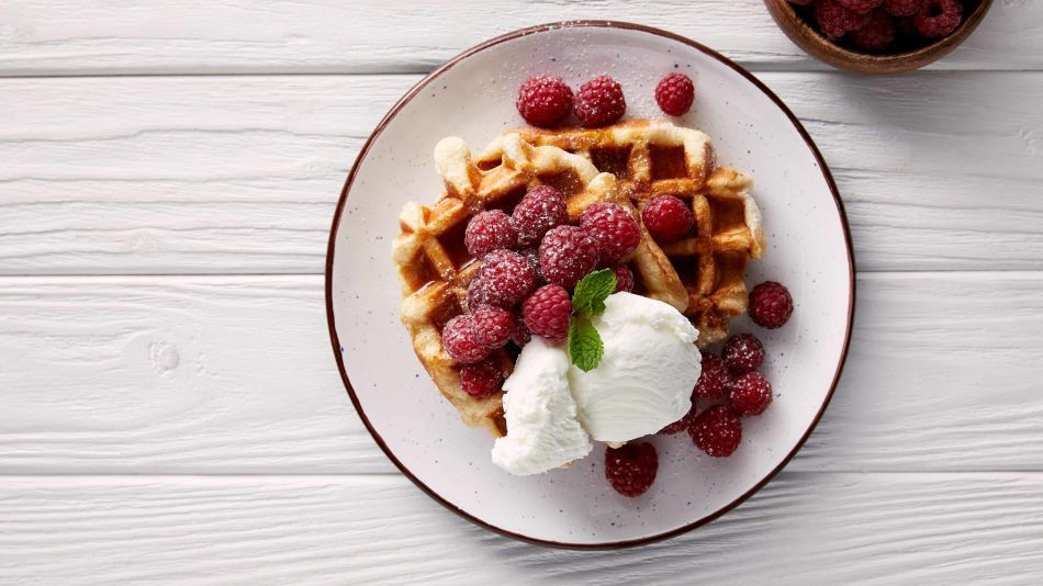 Belgian waffles.jpg - belgian waffles with rasperries and vanilla ice on a white plate.