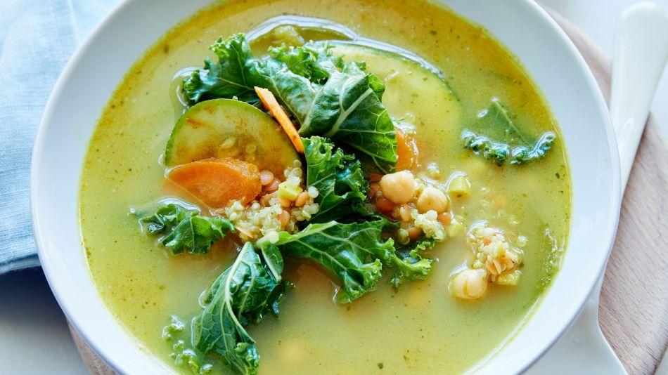 Grüne Gemüsesuppe mit Kichererbsen - Groene groentesoep met kekers bereid in een witte soepkom met een lepel