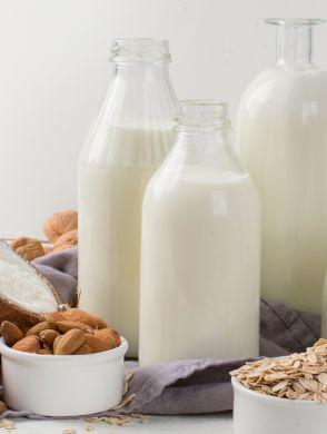 Faktencheck-Milchalternativen - Mehrere Flaschen mit Milchalternativen und verschiedene Nusssorten stehen auf einem Tisch