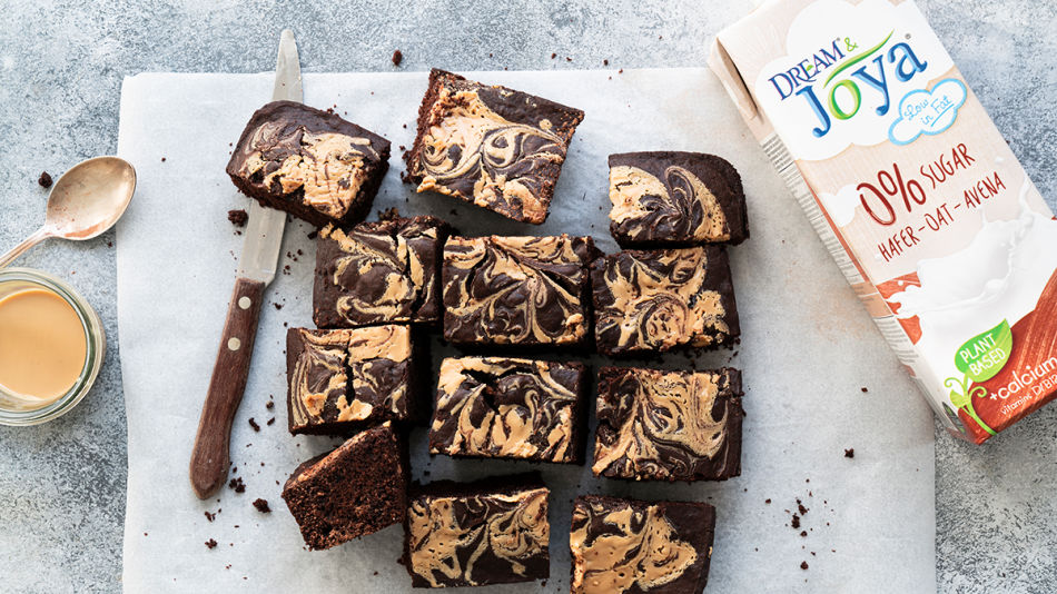 Zero-Peanut-Brownies-2 - Several pieces of Zero Sugar Brownies on a white chopping board with a bowl of peanut and Joya 0% Sugar Oat Drink