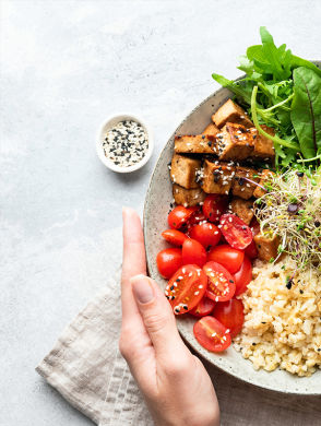 Pflanzliche Protein Bowl - Plate with various vegetables, fried tofu and rice on white background.