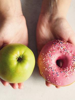 Balance beim Essen - 2 handen op een lichte achtergrond, een met een appel, de andere met een donut met roze glazuur
