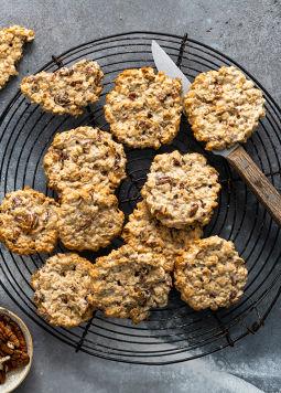 Hafer Pecan Kekse - Sommige koekjes van haverpecannoten liggen op een rond rooster om af te koelen, daarnaast zie je de Dream & Joya haverdrank 0% suiker