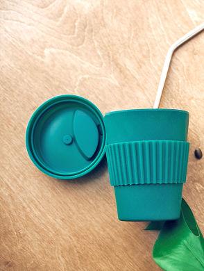Nachhaltiger Kaffeekonsum - Groene herbruikbare beker met metalen rietje op houten tafel, met een paar koffiebonen en een blad