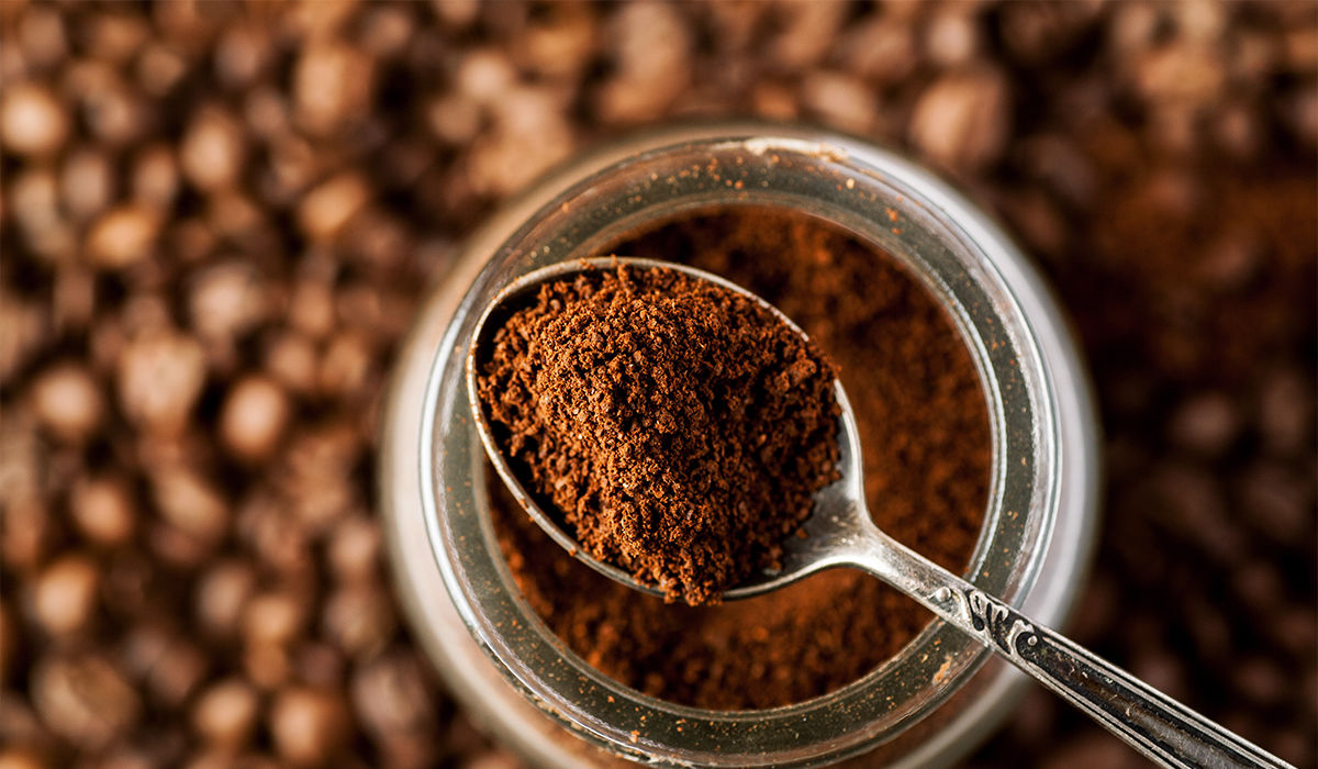 8 Arten, um Kaffeesatz wiederzuverwenden - A spoonful of coffee powder lies on a glass with coffee powder, coffee beans can be seen in the background