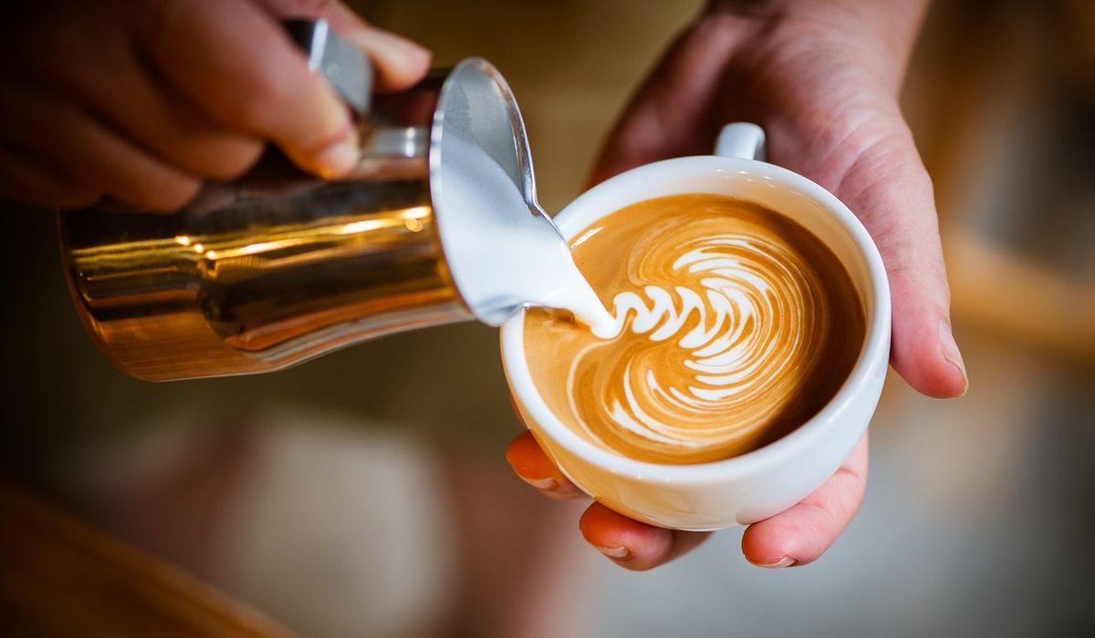 Kaffee mit pflanzlicher Milch - Milchschaum wird in eine Tasse Kaffe gegossen. - © Shutterstock