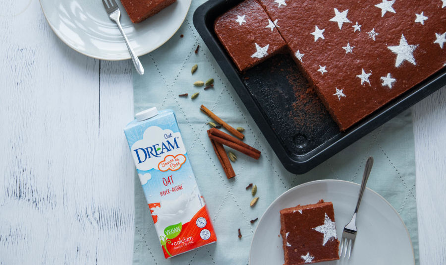 DR_Gingerbread-Cake - A gingerbread cake in a baking form next to a package of Dream Oat Drink on a white table with two plates of ginger bread cake.
