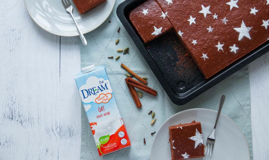 DR_Gingerbread-Cake - Een peperkoekcake in bakvorm naast een pakje Dream Oat Drink op een witte tafel met twee borden gemberbroodcake.