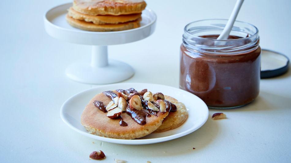 Chocolate-Hazelnut-Spread - Schoko-Haselnuss-Auftrich in einem Glas und zwei Teller mit Pancakes, Aufstrich und Haselnüssen - © Have a Dream