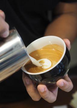 Kaffeetrends-Flat White-Joya - Milchschaum wird in eine Tasse Kaffee gegossen - © Shutterstock