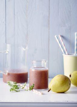 smoothie with strawberry pear and kale - un pot et un verre avec un smoothie avec fraise, poire et chou frisé sur une table blanche