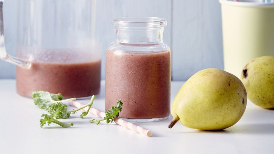 smoothie with strawberry pear and kale - A jar and a glass with smoothie of strawberry, pear and kale on a white table